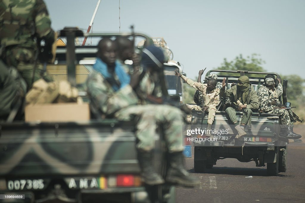 Malian soldiers sit in pick ups on their way to Niono, 340km north from Bamako, on January 18, 2013 in Markala. France confirmed today that Malian troops had taken control of the key central town of Konna from armed Islamists who seized the country's vast desert north in April last year.AFP PHOTO / FRED DUFOUR