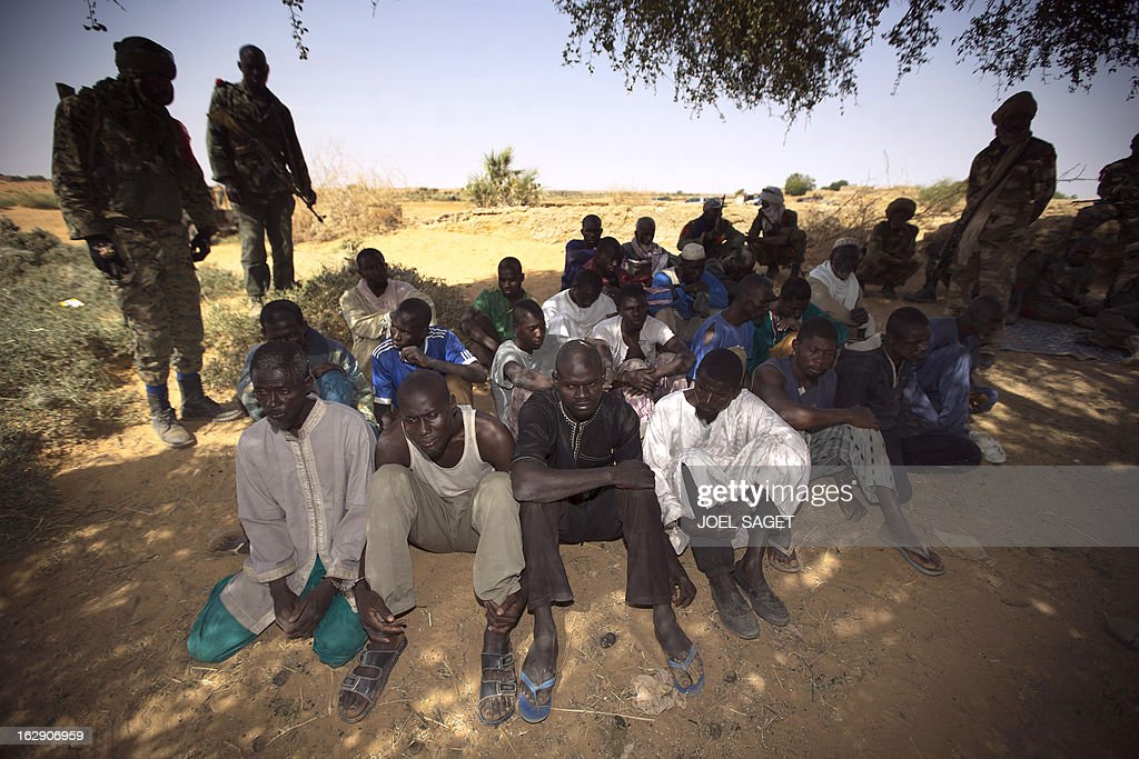 Malian soldiers stand by prisoners after they arrived by boat in Kadji, on the Niger river on March 1, 2013. French and Malian troops launched an operation yesterday in the village of Kadji, northern Mali, where Islamists are hiding out on an island in the Niger river, a military source told AFP.