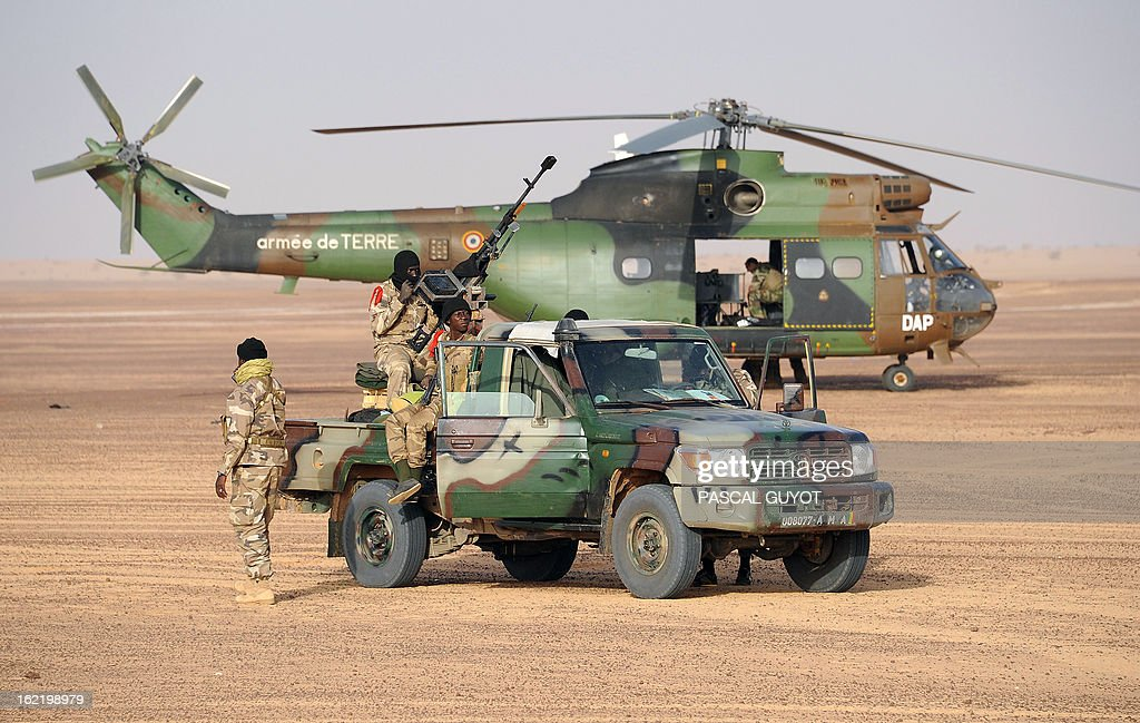 Malian soldiers stand on a pick-up truck next to a French army Puma helicopter on February 17, 2013 in Bourem, northern Mali. A French-led military intervention launched on January 11 has driven the Islamist rebels in Mali from the towns they controlled, but concerns remain over stability amid suicide attacks and guerrilla fighting. GUYOT
