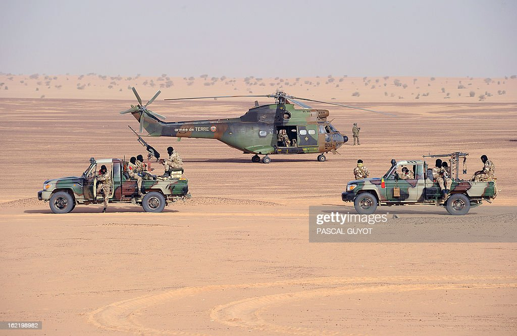 Malian soldiers stand on pick-up trucks next to a French army Puma helicopter on February 17, 2013 in Bourem, northern Mali. A French-led military intervention launched on January 11 has driven the Islamist rebels in Mali from the towns they controlled, but concerns remain over stability amid suicide attacks and guerrilla fighting. GUYOT