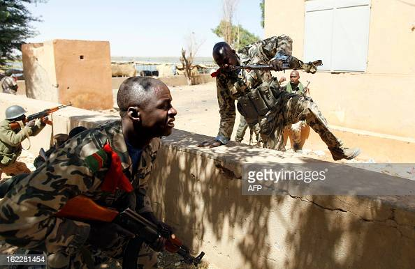 Malian soldiers take cover as they fight while clashes erupted in the city of Gao on February 21 2013 and an apparent car bomb struck near a camp...