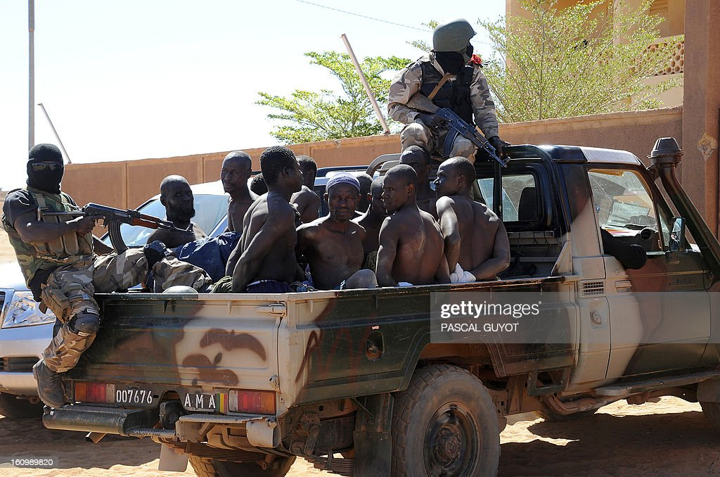 Malian soldiers transport in a pickup truck a dozen suspected Islamist rebels on February 8, 2013 after arresting them north of Gao. A suicide bomber blew himself up on February 8 near a group of Malian soldiers in the northern city of Gao, where Islamist rebels driven from the town have resorted to guerilla attacks The act marked the first suicide attack in the embattled west African nation since the start of a French-led offensive to oust the Islamists from Mali's north, where they had controlled key towns for 10 months.