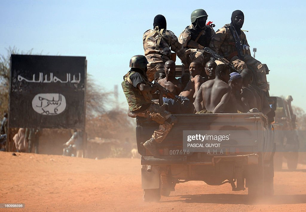Malian soldiers transport in a pickup truck a dozen suspected Islamist rebels on February 8, 2013 after arresting them north of Gao. A suicide bomber blew himself up on February 8 near a group of Malian soldiers in the northern city of Gao, where Islamist rebels driven from the town have resorted to guerilla attacks The act marked the first suicide attack in the embattled west African nation since the start of a French-led offensive to oust the Islamists from Mali's north, where they had controlled key towns for 10 months. A billboard (L) left by unidentified Islamists reads: 'There's not God but God and Mohammed is his prophet'.