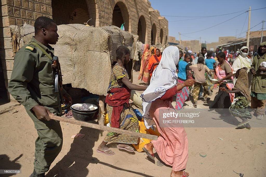 A Malian soldiers tries to disperse the crowd on January 29, 2013 in Timbuktu as residents plunder stores they say belong to Arabs, Mauritanians and Algerians who they accuse of supporting the Al Qaeda-linked Islamists during their 10-month rule over the ancient centre of Islamic learning. French-led troops freed the northern desert city on January 28 from Islamist control. Hundreds of Malians looted Arab-owned shops on January 29 in Timbuktu as global donors pledged over 455 million US dollars (340 million euro) at a donor conference in the Ethiopian capital Addis Ababa for military operations in Mali and humanitarian aid to rout the radicals from the north.