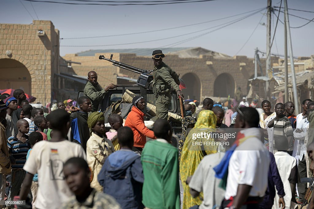 Malian soldiers try to disperse the crowd on January 29, 2013 in Timbuktu as residents plunder stores they say belong to Arabs, Mauritanians and Algerians who they accuse of supporting the Al Qaeda-linked Islamists during their 10-month rule over the ancient centre of Islamic learning. French-led troops freed the northern desert city on January 28 from Islamist control. Hundreds of Malians looted Arab-owned shops on January 29 in Timbuktu as global donors pledged over 455 million US dollars (340 million euro) at a donor conference in the Ethiopian capital Addis Ababa for military operations in Mali and humanitarian aid to rout the radicals from the north.
