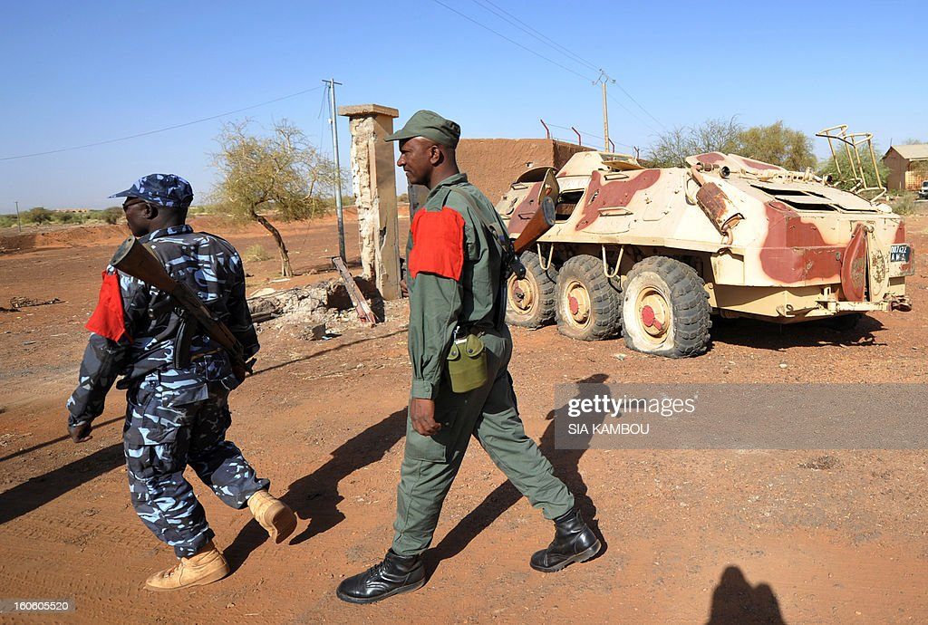 Malian soldiers walk on February 3, 2013 in Gao, near an armoured vehicle they abandoned when Islamist extremists took the city on March 31, 2012. France said it carried out major air strikes today near Kidal, the last bastion of armed extremists chased from Mali's desert north in a lightning French-led offensive.