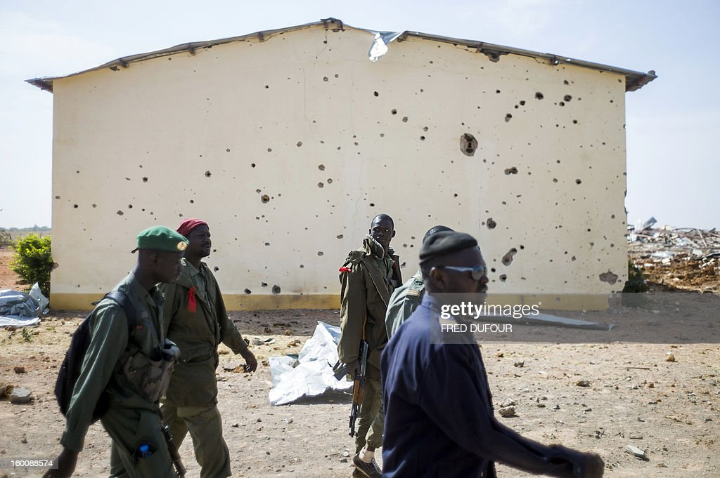 Malian soldiers walk past the bullet ridden wall of a house in a destroyed area of Konna on January 26, 2013. French-led forces today wrested control of the airport at the Islamist stronghold of Gao, 1,200 kilometres (750 miles) northeast of the Mali capital Bamako, a security source said.