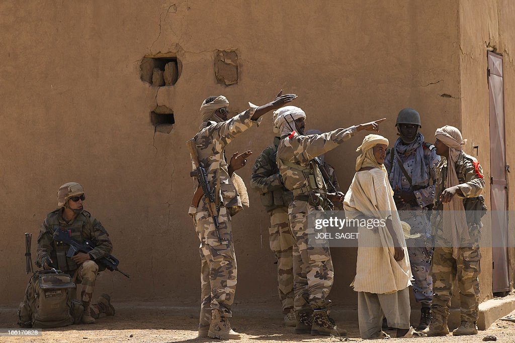 A Malian Special Force soldier and a French soldier question people during the Operation Gustav, a hunt for Islamist fighters in a valley in northern Mali and one of France's largest military operations during its three-month intervention in its former colony, on April 9, 2013, 105 km North of Gao. Operation Gustav comes with France preparing to withdraw three-quarters of the 4,000 troops it deployed in January to block a feared advance on the Malian capital Bamako by Al Qaeda-linked insurgents. AFP PHOTO / JOEL SAGET