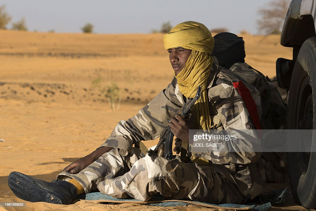 A malian Special Force soldier holds a gun as she sits on the ground, during the Operation Gustav, a hunt for Islamist fighters in a valley in northern Mali and one of France's largest military operations during its three-month intervention in its former colony, on April 9, 2013, 105 km North of Gao. Operation Gustav comes with France preparing to withdraw three-quarters of the 4,000 troops it deployed in January to block a feared advance on the Malian capital Bamako by Al Qaeda-linked insurgents.
