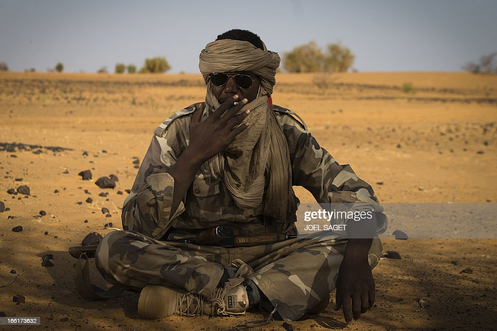A Malian Special Force soldier smokes a cigarette 105 kms north of the northeastern Malian city of Gao on April 9, 2013 during day two of Operation Gustav, a hunt for Islamist fighters in a valley in northern Mali and one of France's largest military operations during its three-month intervention in its former colony. Operation Gustav comes with France preparing to withdraw three-quarters of the 4,000 troops it deployed in January to block a feared advance on the Malian capital Bamako by Al Qaeda-linked insurgents. AFP PHOTO / JOEL SAGET