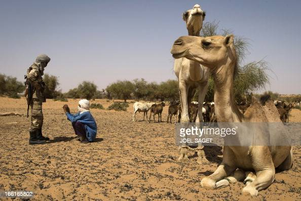 A malian Special Force soldier speaks to a child during the Operation Gustav a hunt for Islamist fighters in a valley in northern Mali and one of...