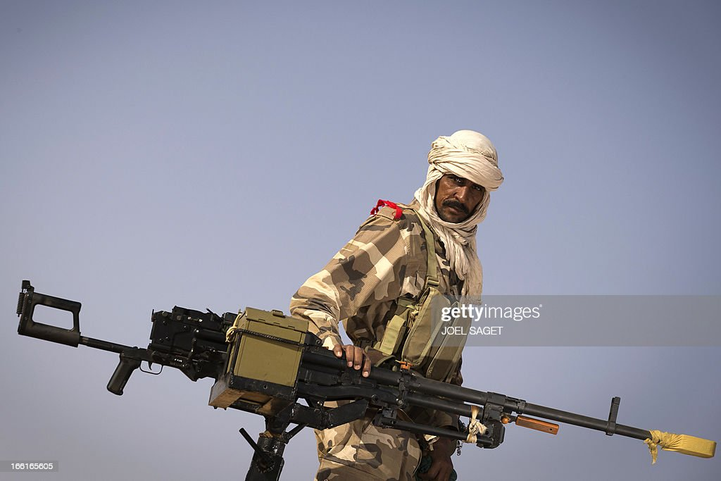 A malian Special Force soldier stands next to a machine gun during the Operation Gustav, a hunt for Islamist fighters in a valley in northern Mali and one of France's largest military operations during its three-month intervention in its former colony, on April 9, 2013, 105 km North of Gao. Operation Gustav comes with France preparing to withdraw three-quarters of the 4,000 troops it deployed in January to block a feared advance on the Malian capital Bamako by Al Qaeda-linked insurgents. AFP PHOTO / JOEL SAGET