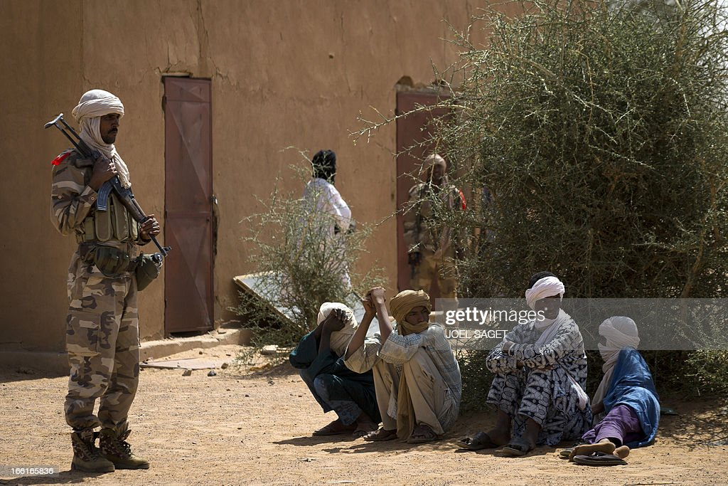 A malian Special Force soldier stands next to people sitting on the ground during the Operation Gustav, a hunt for Islamist fighters in a valley in northern Mali and one of France's largest military operations during its three-month intervention in its former colony, on April 9, 2013, 105 km North of Gao. Operation Gustav comes with France preparing to withdraw three-quarters of the 4,000 troops it deployed in January to block a feared advance on the Malian capital Bamako by Al Qaeda-linked insurgents. AFP PHOTO / JOEL SAGET