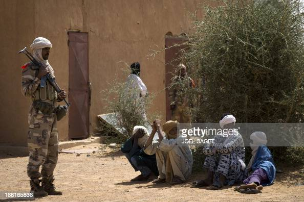 A malian Special Force soldier stands next to people sitting on the ground during the Operation Gustav a hunt for Islamist fighters in a valley in...