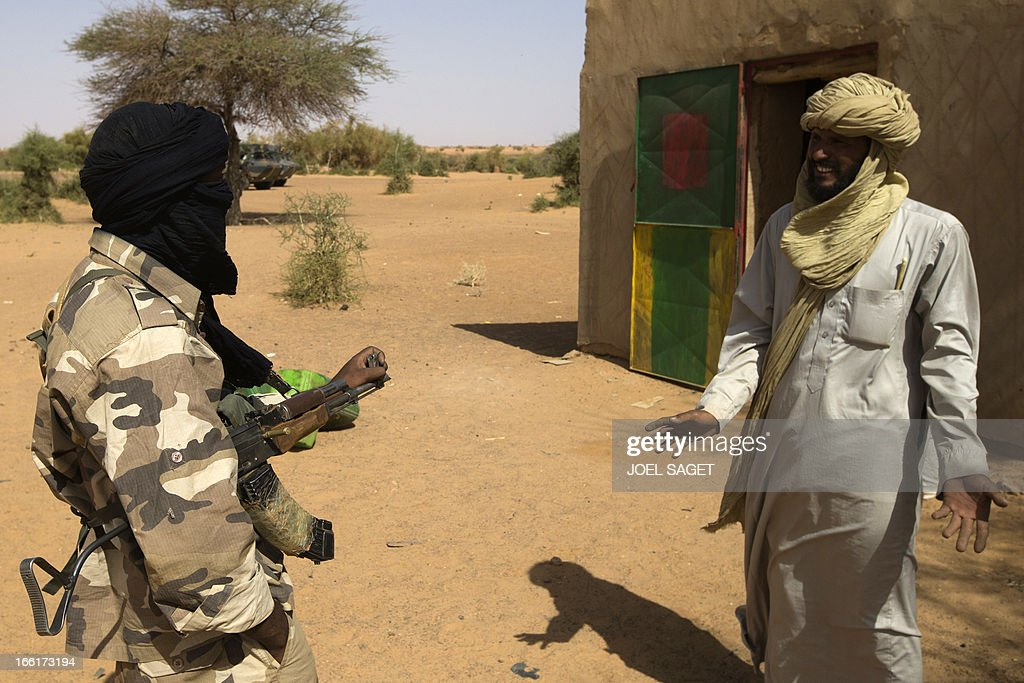 Malian Special Forces soldier speaks with a Malian during the Operation Gustav, a hunt for Islamist fighters in a valley in northern Mali and one of France's largest military operations during its three-month intervention in its former colony, on April 9, 2013, 105 km North of Gao. Operation Gustav comes with France preparing to withdraw three-quarters of the 4,000 troops it deployed in January to block a feared advance on the Malian capital Bamako by Al Qaeda-linked insurgents. AFP PHOTO / JOEL SAGET