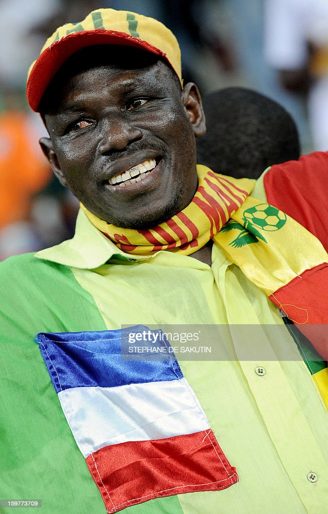 A Malian team supporter wearing a small French flag and a Malian flag on each side of his jacket cheers during the 2013 African Cup of Nations football match between Mali and Niger at the Nelson Mandela Bay Stadium in Port Elizabeth on January 20, 2013.