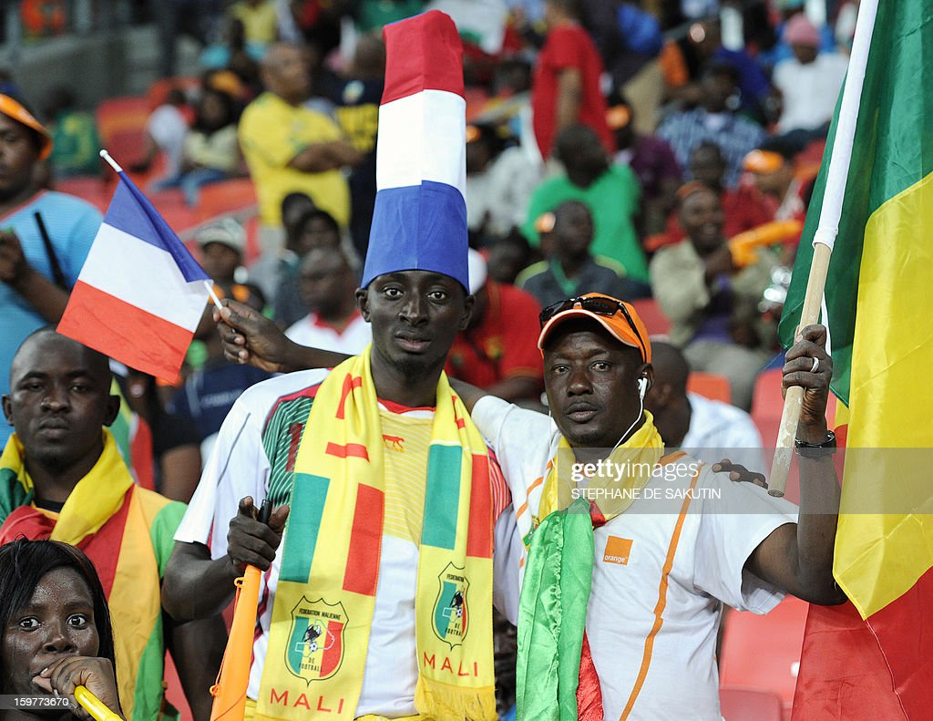 A Malian team supporter wears a hat shaped as a French flag as another man holds a French flag in one hand and a Malian flag in the other, during the 2013 African Cup of Nations football match between Mali and Niger at the Nelson Mandela Bay Stadium in Port Elizabeth on January 20, 2013.