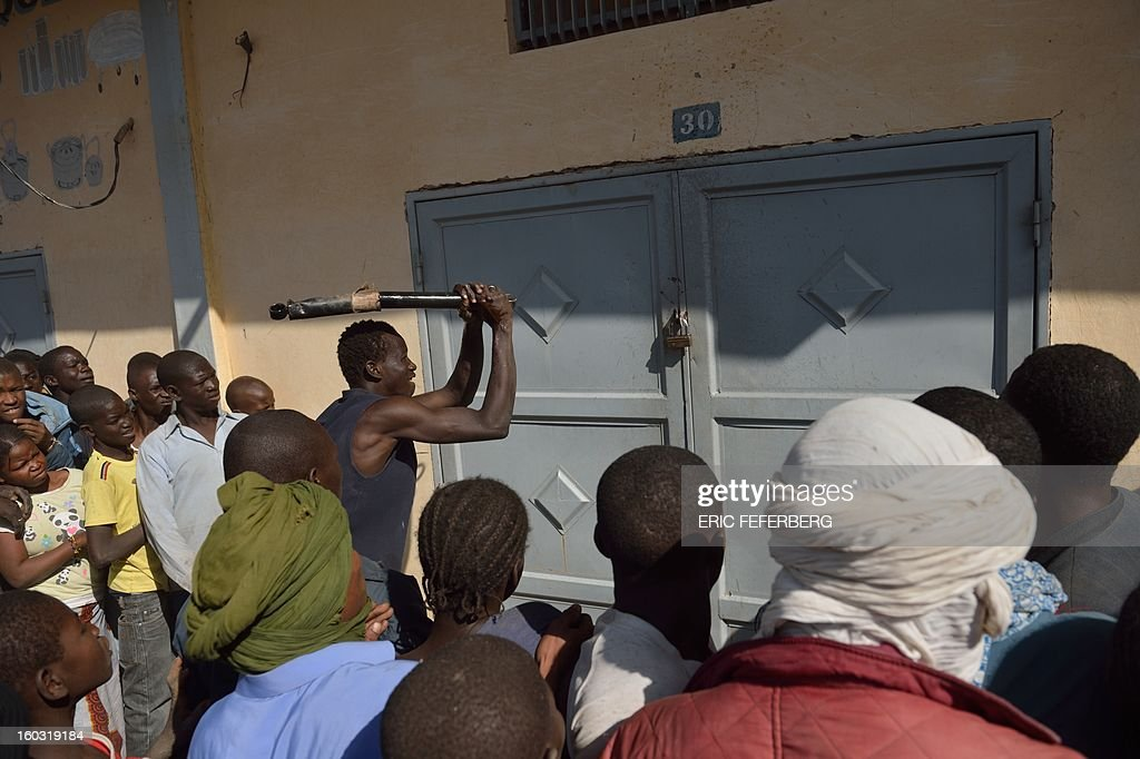 A Malian tries to break the lock off a store front as looters and residents stand by in the streets of Timbuktu on January 29, 2013. Hundreds of Malians looted stores in Timbuktu on Tuesday, saying the shops belonged to 'Arabs' and 'terrorists' linked to the radical Islamists who occupied the desert town for 10 months.