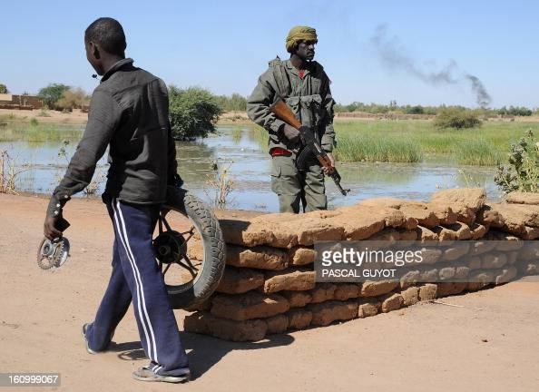 A Malian walks past a Malian Army checkpoint on February 8 2013 at the site where a suicide bomber blew himself up earlier in the day near a group of...
