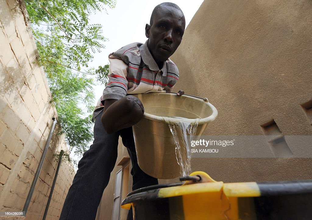 A Malian, who was amputated for alleged theft by Islamists of the Movement for Oneness and Jihad in West Africa (MUJAO), pours water in a courtyard on January 31, 2013 in the northern Malian city of Gao. The city was controlled by Islamists who applied Islamic sharia law with public punishments, including stoning and amputation of limbs. Gao was retaken on January 26 by French and Malian troops in a major boost to the French-led offensive against the Al Qaeda-linked rebels, who have been holding Mali's vast desert north since last April. FP