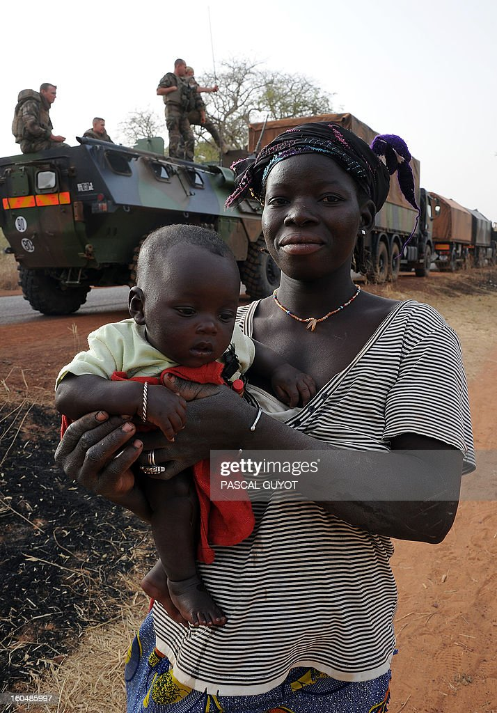 A Malian woman carries her child as she walks by a convoy of French army vehicules arriving in Sevare, in the Mopti region of Mali, on February 1, 2013. President Francois Hollande prepared to visit Mali as French-led troops worked today to secure the last Islamist stronghold in the north after a lightning offensive against the extremists. Hollande, whose surprise decision to intervene in Mali three weeks ago has won broad support at home, will travel to the fabled city of Timbuktu and hold a working lunch in the capital with Mali's interim president Dioncounda Traore, the Malian presidency said.