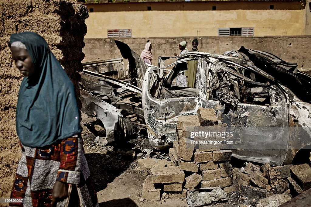 A Malian woman passes the wreckage of a vehicle that was destroyed in a French airstrike on January 21, 2013 near Diabaly, Mali. For the last week, French and Malian forces fought to route Islamic militants from the town.