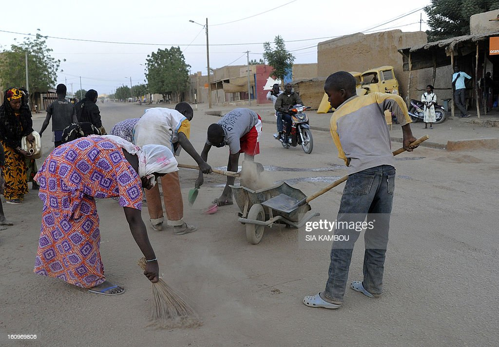 Malian women and youths clean a street on February 7, 2013 in the northern city of Gao. A suicide bomber blew himself up on February 8 near a group of Malian soldiers in Gao, where Islamist rebels driven from the town have resorted to guerilla attacks. The act marked the first suicide attack in the embattled west African nation since the start of a French-led offensive to oust the Islamists from Mali's north, where they had controlled key towns for 10 months.