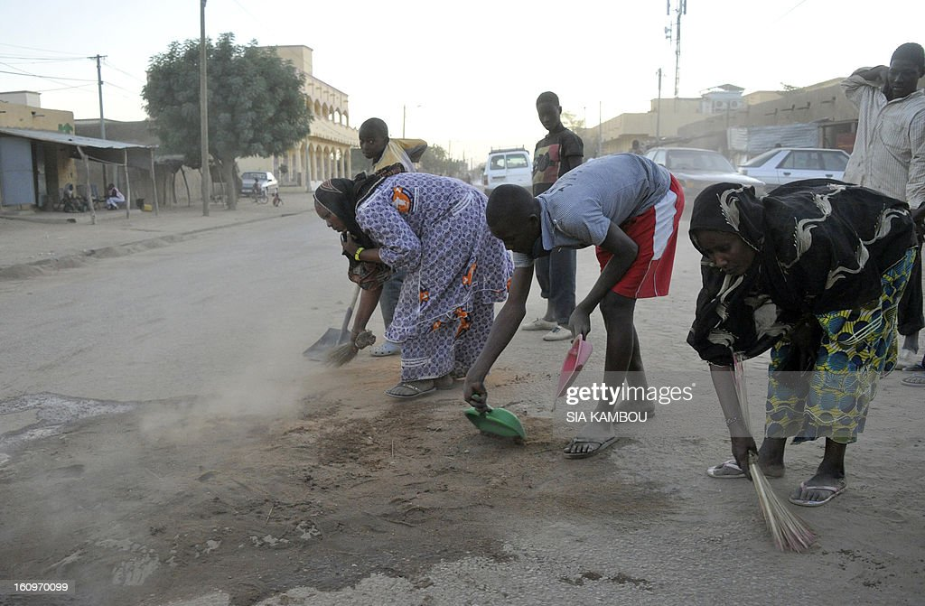 Malian women and youths clean a street on February 7, 2013 in the northern city of Gao. A suicide bomber blew himself up on February 8 near a group of Malian soldiers in Gao, where Islamist rebels driven from the town have resorted to guerilla attacks. The act marked the first suicide attack in the embattled west African nation since the start of a French-led offensive to oust the Islamists from Mali's north, where they had controlled key towns for 10 months. AFP PHOTO / SIA KAMBOU
