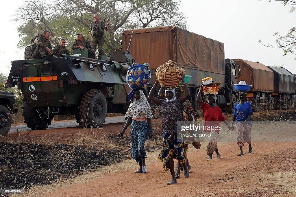 Malian women walk by a convoy of French army vehicules as French soldiers arrive in Sevare, in the Mopti region of Mali, on February 1, 2013. President Francois Hollande prepared to visit Mali as French-led troops worked today to secure the last Islamist stronghold in the north after a lightning offensive against the extremists. Hollande, whose surprise decision to intervene in Mali three weeks ago has won broad support at home, will travel to the fabled city of Timbuktu and hold a working lunch in the capital with Mali's interim president Dioncounda Traore, the Malian presidency said.
