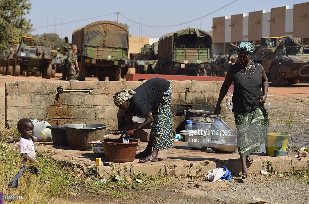 Malian women wash dishes inside the Malian army 101 airbase where French troops from 21st Rima are stationed on January 18, 2013, near Bamako. France now has 1,800 troops on the ground in Mali, inching closer to the goal of 2,500 it plans to deploy in its African former colony, Defence Minister Jean-Yves Le Drian said today. That was 400 more than a day earlier, said the minister as he met with French special forces in the western port of Lorient. The troops have been sent to help the Malian army regain control of the north from Islamist groups.