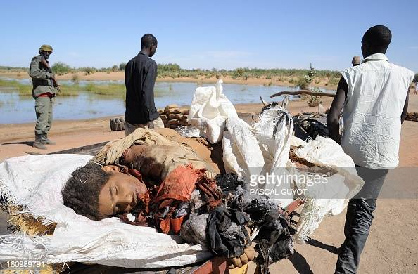 Malians carry on February 8 2013 the corpse of a suicide bomber who blew himself up near a group of Malian soldiers in the northern city of Gao where...