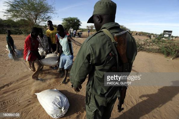 Malians carry sand bags as they consolidate a Malian Army checkpoint on February 8 2013 at the site where a suicide bomber blew himself up earlier in...