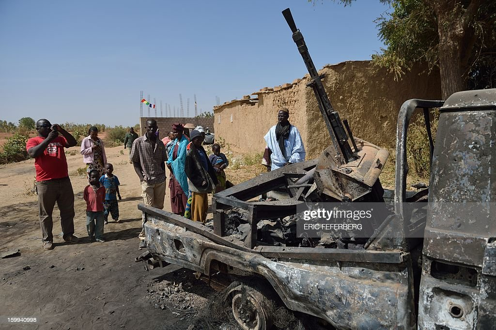 Malians continue to gather round the remains of an Islamists pickup on January 23, 2013 that was destroyed by a French air strike in Diabaly (400km north of Bamako). AFP/PHOTO ERIC FEFERBERG