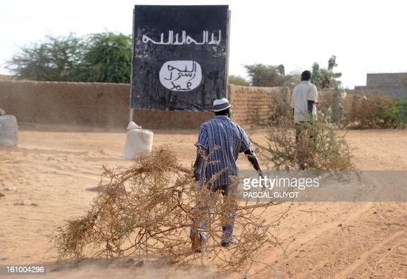 Malians draw trees branches they will use to consolidate a Malian Army checkpoint on February 8 2013 at the site where a suicide bomber blew himself...