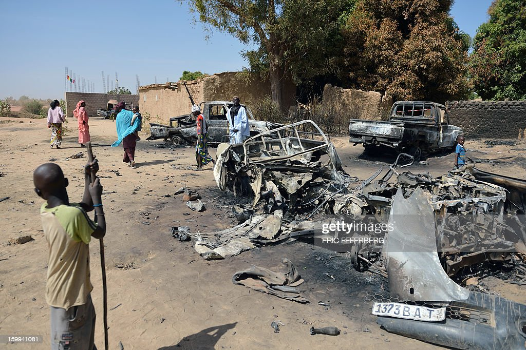 Malians gather round the remains of destroyed Islamists vehicles destroyed by an earlier French air strike on January 23, 2013 in Diabaly (400km north of Bamako). AFP PHOTO /ERIC FEFERBERG