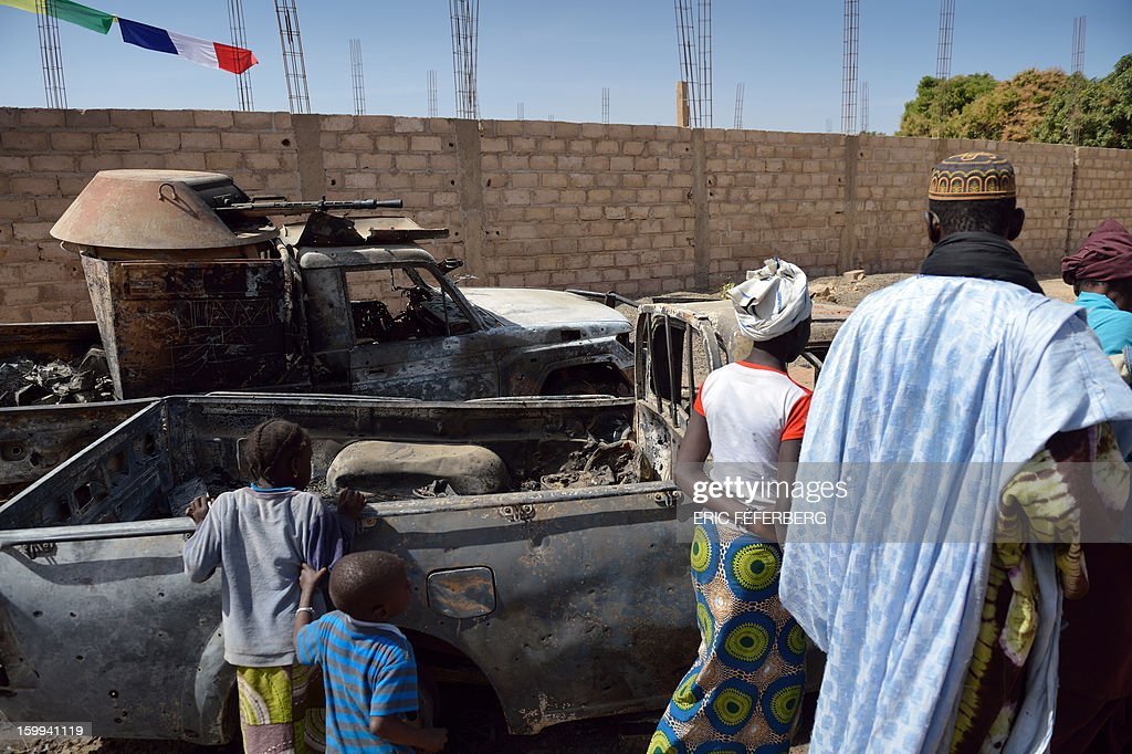 Malians gather round the remains of destroyed Islamists vehicles destroyed by an earlier French air strike on January 23, 2013 in Diabaly (400km north of Bamako).