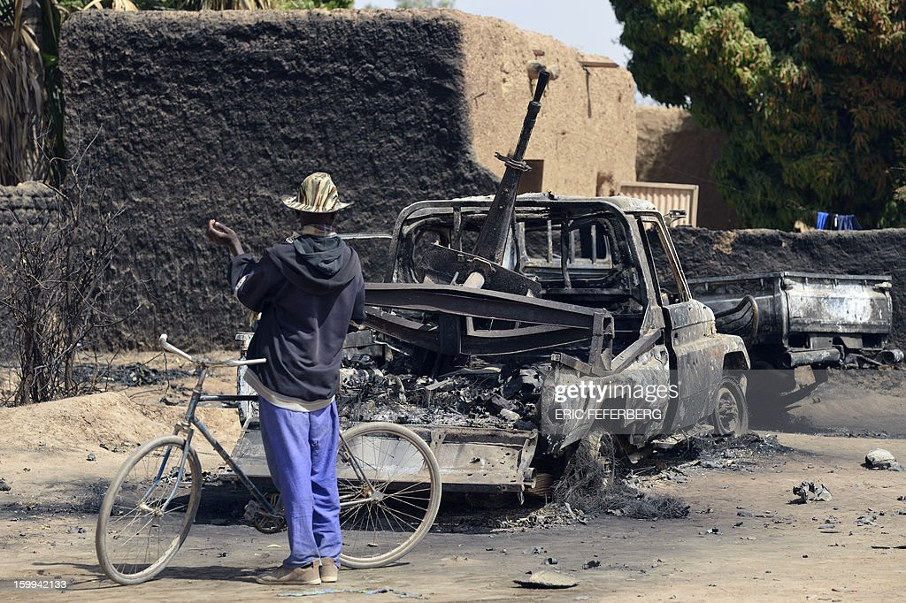Malians gather round the remains of Islamists vehicles destroyed by an earlier French air strike on January 23, 2013 in Diabaly (400km north of Bamako).