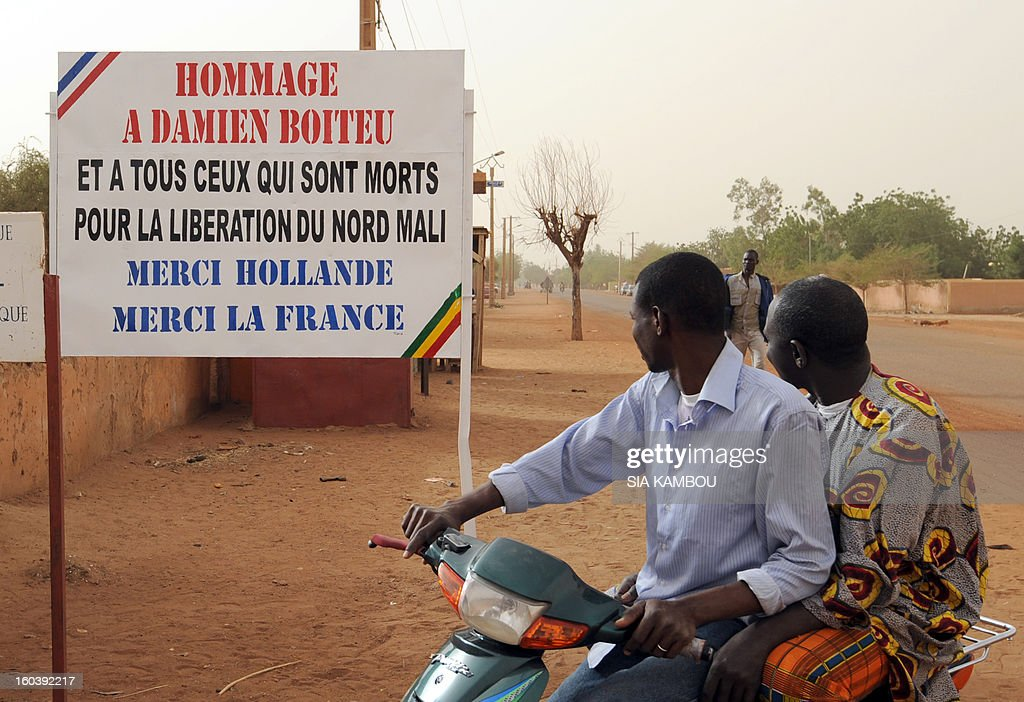 Malians look at a billboard on January 30, 2013, reading:'Homage to Damien Boiteu (a French helicopter pilot killed on January 11) and to all those who died to free northern Mali -- Thank you (French President Francois) Hollande, Thank you France,' in the northern city of Gao, a key Islamist stronghold until it was retaken on January 26 by French and Malian troops in a major boost to the French-led offensive against the Al Qaeda-linked rebels, who have been holding Mali's vast desert north since last April. French troops on January 30 entered Kidal, the last Islamist bastion in Mali's north after a whirlwind Paris-led offensive, as France urged peace talks to douse ethnic tensions targeting Arabs and Tuaregs. AFP PHOTO/ SIA KAMBOU