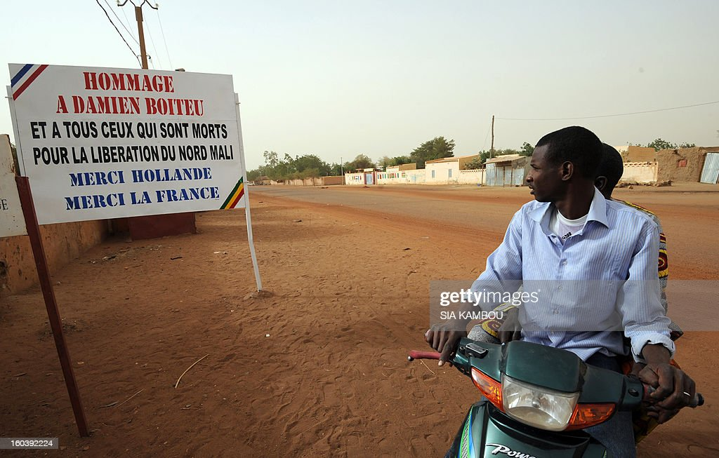 Malians look at a billboard on January 30, 2013, reading:'Homage to Damien Boiteu (a French helicopter pilot killed on January 11) and to all those who died to free northern Mali -- Thank you (French President Francois) Hollande, Thank you France,' in the northern city of Gao, a key Islamist stronghold until it was retaken on January 26 by French and Malian troops in a major boost to the French-led offensive against the Al Qaeda-linked rebels, who have been holding Mali's vast desert north since last April. French troops on January 30 entered Kidal, the last Islamist bastion in Mali's north after a whirlwind Paris-led offensive, as France urged peace talks to douse ethnic tensions targeting Arabs and Tuaregs.