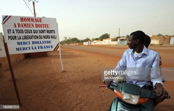 Malians look at a billboard on January 30 reading'Homage to Damien Boiteu and to all those who died to free northern Mali Thank you Hollande Thank...