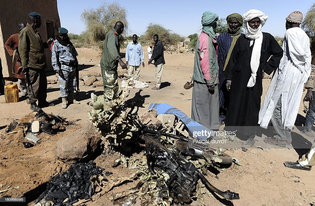 Malians look on February 8, 2013 at the charred motorcycle used by a suicide bomber before he blew himself up near a group of Malian soldiers in the northern city of Gao, where Islamist rebels driven from the town have resorted to guerilla attacks The act marked the first suicide attack in the embattled west African nation since the start of a French-led offensive to oust the Islamists from Mali's north, where they had controlled key towns for 10 months.