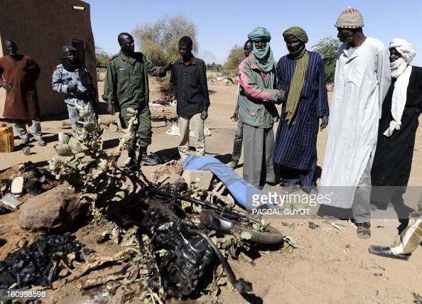 Malians look on February 8 2013 at the charred motorcycle used by a suicide bomber before he blew himself up near a group of Malian soldiers in the...