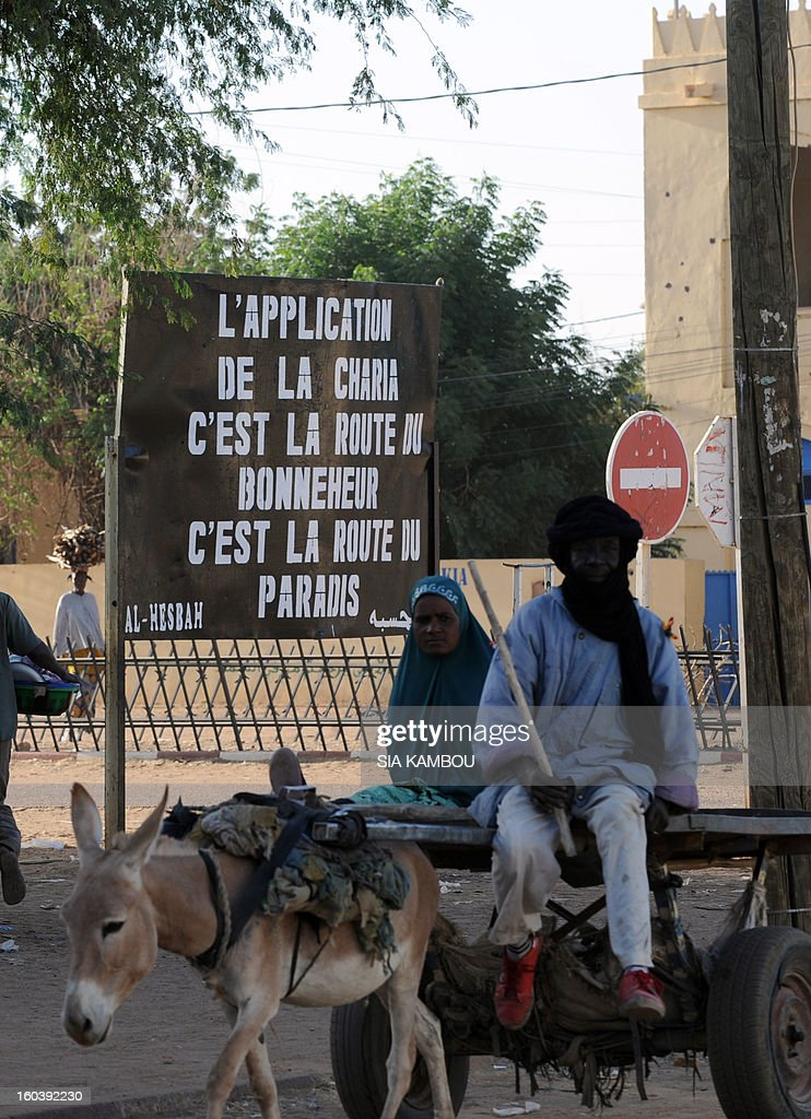 Malians pass a billboard left by the Movement for Oneness and Jihad in West Africa (MUJAO), an offshoot of Al Qaeda in the Islamic Maghreb (AQIM), on January 30, 2013, reading :'Enforcing Sharia is the road to happiness, it is the road to paradise,' in the northern city of Gao, a key Islamist stronghold until it was retaken on January 26 by French and Malian troops in a major boost to the French-led offensive against the Al Qaeda-linked rebels, who have been holding Mali's vast desert north since last April. French troops on January 30 entered Kidal, the last Islamist bastion in Mali's north after a whirlwind Paris-led offensive, as France urged peace talks to douse ethnic tensions targeting Arabs and Tuaregs.