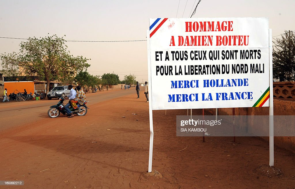 Malians pass by a billboard on January 30, 2013, reading:'Homage to Damien Boiteu (a French helicopter pilot killed on January 11) and to all those who died to free northern Mali -- Thank you (French President Francois) Hollande, Thank you France,' in the northern city of Gao, a key Islamist stronghold until it was retaken on January 26 by French and Malian troops in a major boost to the French-led offensive against the Al Qaeda-linked rebels, who have been holding Mali's vast desert north since last April. French troops on January 30 entered Kidal, the last Islamist bastion in Mali's north after a whirlwind Paris-led offensive, as France urged peace talks to douse ethnic tensions targeting Arabs and Tuaregs.