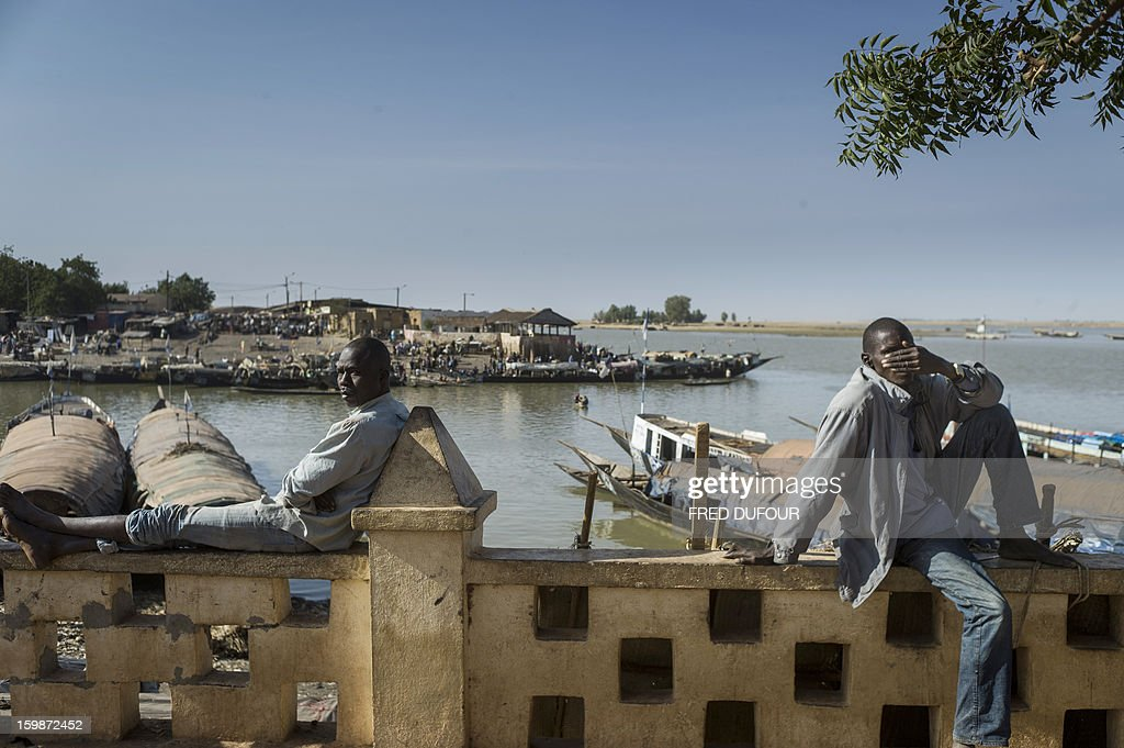 Malians sit on a wall along the Niger River in Mopti on January 22, 2013. The EU executive today announced 20 million euros of extra humanitarian aid to help tens of thousands of Malians fleeing fighting in the nation's north and centre, its second such donation in as many months.