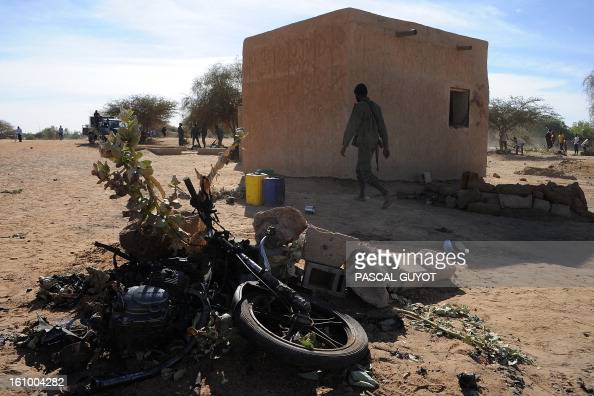 Malians walk on February 8 2013 past the charred motorcycle used by a suicide bomber before he blew himself up near a group of Malian soldiers in the...