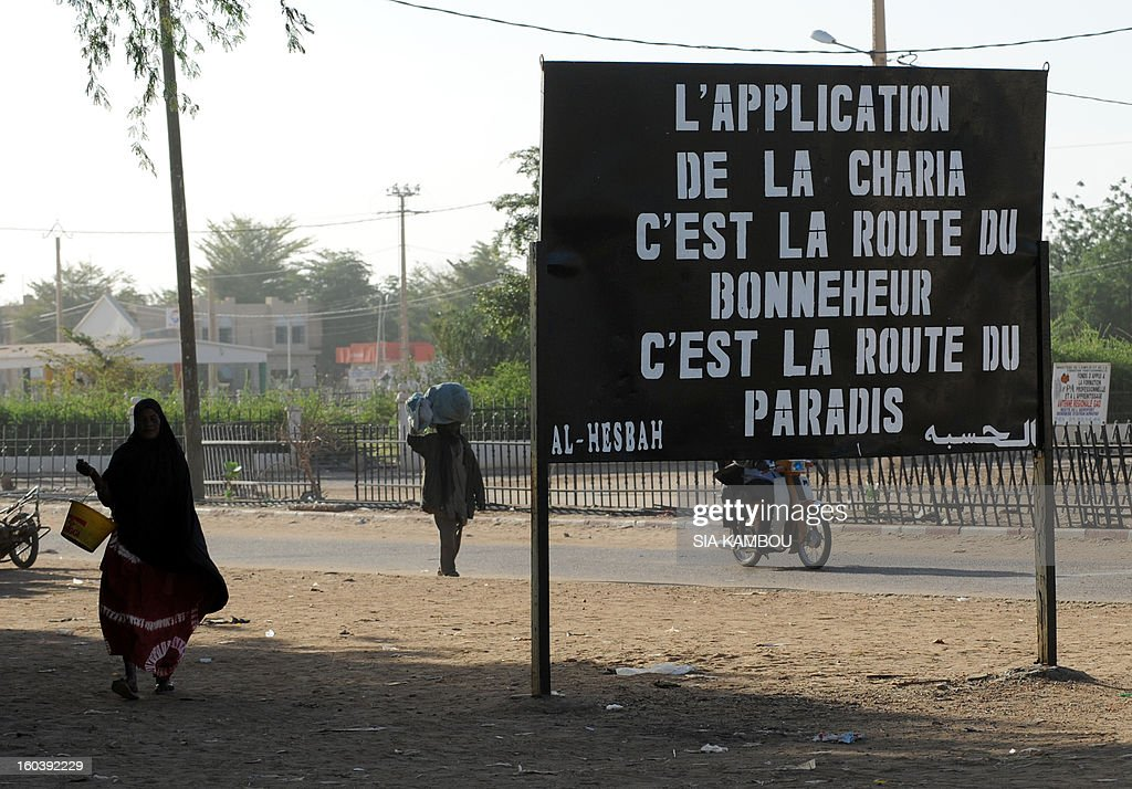 Malians walk past a billboard left by the Movement for Oneness and Jihad in West Africa (MUJAO), an offshoot of Al Qaeda in the Islamic Maghreb (AQIM), on January 30, 2013, reading :'Enforcing Sharia is the road to happiness, it is the road to paradise,' in the northern city of Gao, a key Islamist stronghold until it was retaken on January 26 by French and Malian troops in a major boost to the French-led offensive against the Al Qaeda-linked rebels, who have been holding Mali's vast desert north since last April. French troops on January 30 entered Kidal, the last Islamist bastion in Mali's north after a whirlwind Paris-led offensive, as France urged peace talks to douse ethnic tensions targeting Arabs and Tuaregs.