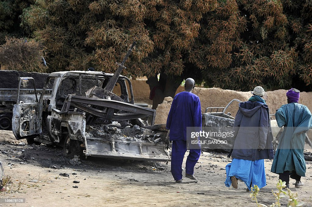 Malians walk past a burnt pickup truck mounted with a machine gun, which was formerly used by Islamists and destroyed after air strikes by the French air force a week ago, at a Malian military base which had been temporarily captured by Islamists, in Diabaly, on January 22, 2013. The EU executive today announced 20 million euros of extra humanitarian aid to help tens of thousands of Malians fleeing fighting in the nation's north and centre, its second such donation in as many months. AFP PHOTO / ISSOUF SANOGO