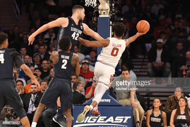 Malik Ellison of the St John's Red Storm drives to the basket around Bradley Hayes of the Georgetown Hoyas during the Big East Basketball Tournament...