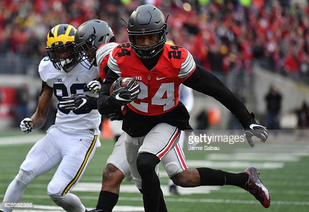 Malik Hooker of the Ohio State Buckeyes runs for a touchdown after intercepting a pass by Wilton Speight of the Michigan Wolverines during the first...